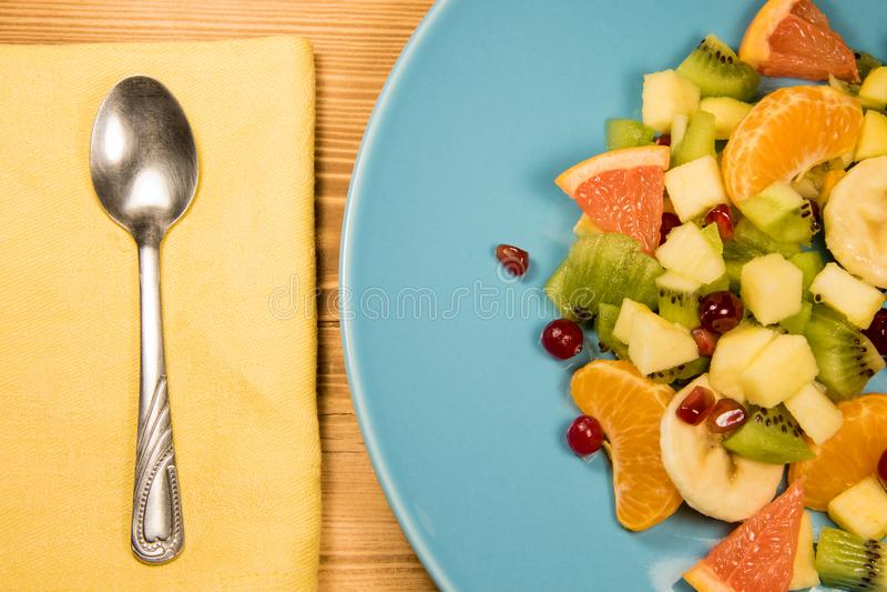 Salada de fruto fresco com citrino em uma placa azul que esteja em uma tabela de madeira com um guardanapo, uma colher e um lugar fotos de stock