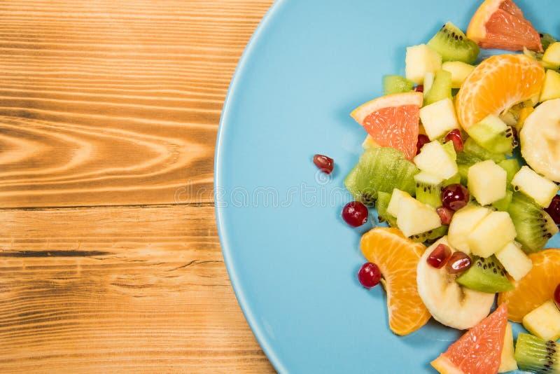 Salada de fruto fresco com citrino em uma placa azul que esteja em uma tabela de madeira com um lugar para a inscrição imagem de stock royalty free