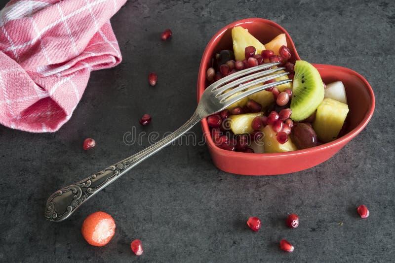 Salada de fruto na bacia da forma do coração imagem de stock