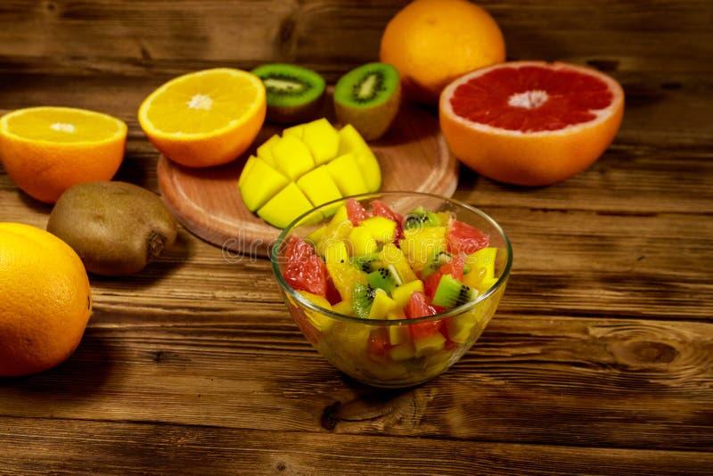 Salada de fruto saboroso na bacia de vidro e em frutos frescos na tabela de madeira fotos de stock royalty free