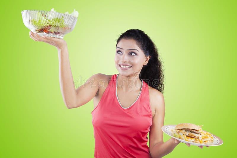 Salada de levantamento e fast food da mulher saudável fotos de stock royalty free