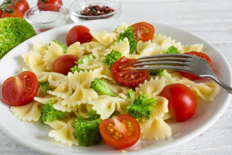 Salada de massa com a cereja dos brócolis e do tomate com forquilha Alimento saudável do vegetariano fotografia de stock