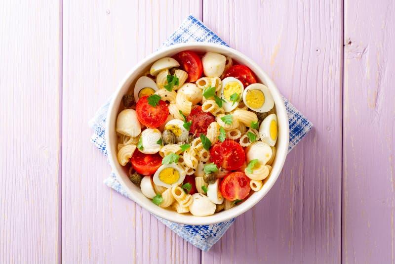Salada de massa com ovos de codorniz, mussarela, tomates de cereja e alcaparras na bacia no fundo de madeira roxo imagens de stock royalty free