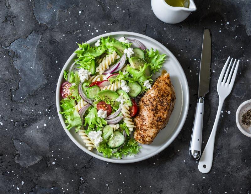 Salada de massa mediterrânea do abacate e peito de frango cozido - almoço equilibrado saudável em um fundo escuro, vista superior fotos de stock royalty free