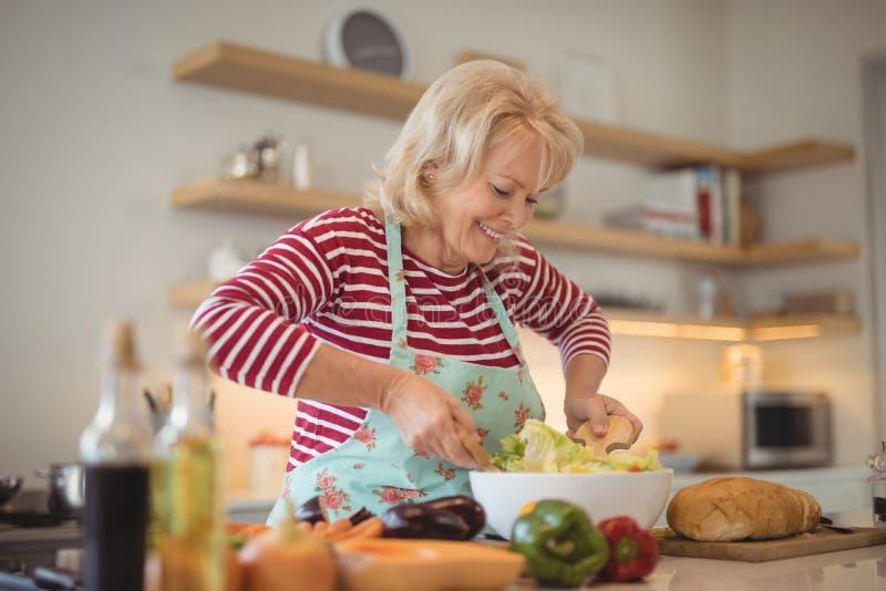 Salada de mistura dos vegetais da mulher superior na cozinha fotografia de stock