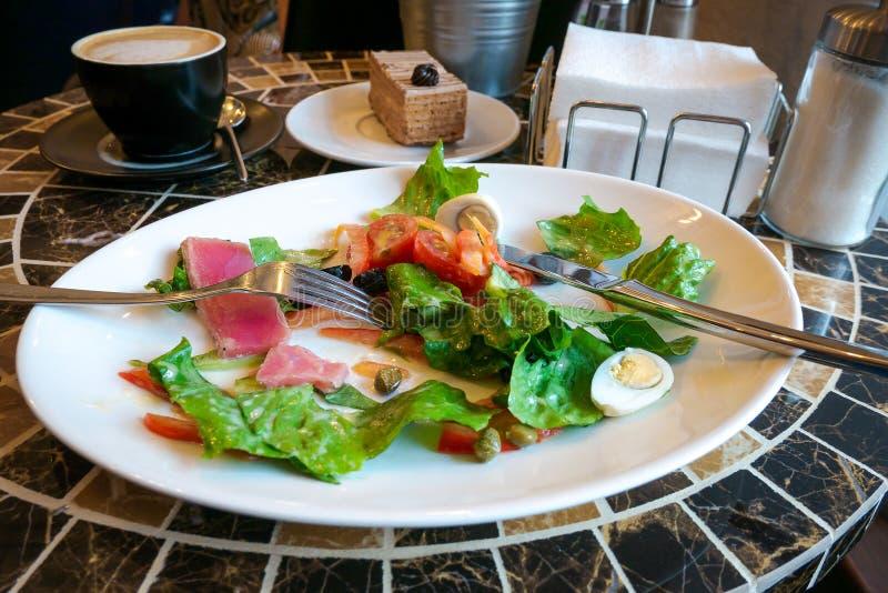 Salada de Nicoise na placa branca, sendo comido com forquilha e faca imagens de stock royalty free