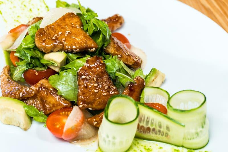 A salada de pepinos e de tomates frescos fritou a carne em uma tabela de madeira imagem de stock