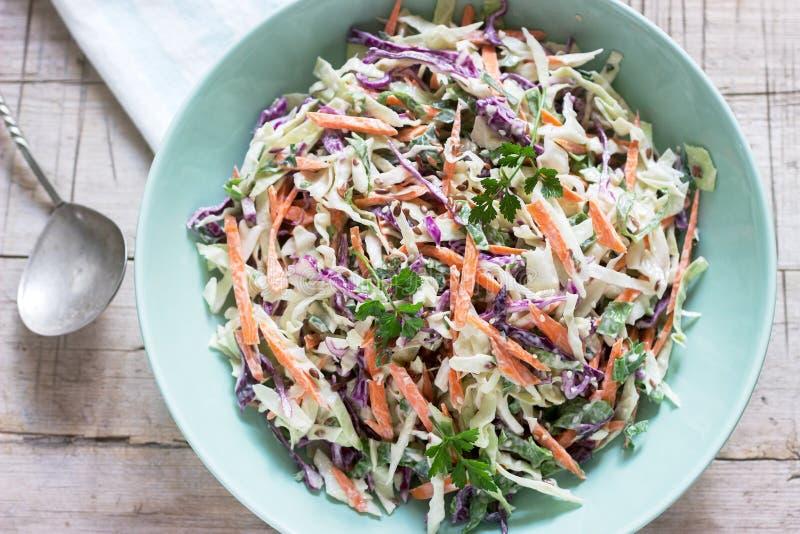 Salada de repolho da couve, das cenouras e de várias ervas com maionese em uma grande placa em um fundo de madeira fotos de stock
