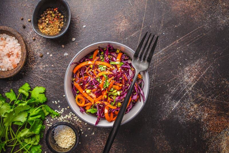 Salada de repolho em uma bacia cinzenta no fundo escuro Salada da couve vermelha e da cenoura fotografia de stock