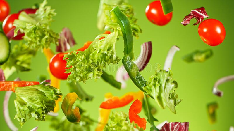 Salada de vegetais voadores isolada em fundo verde imagens de stock royalty free