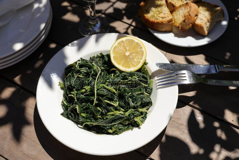 Salada de verdes cozinhada na taberna grega fotografia de stock