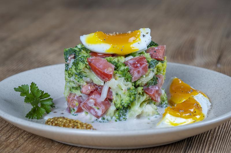 Salada deliciosa com brócolis, tomate, cebola e ovo cozido com molho de creme na placa no fundo de madeira Alimento saud?vel imagem de stock royalty free