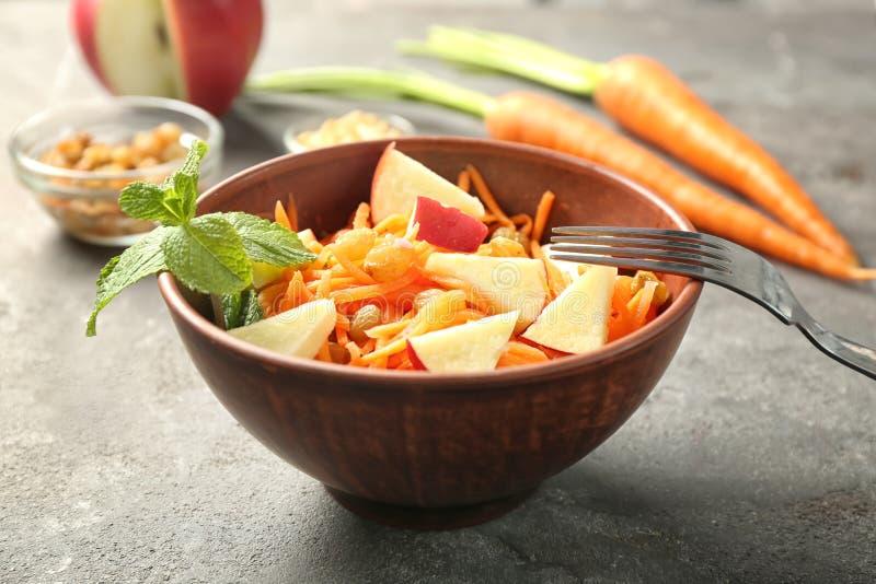 Salada deliciosa da passa da cenoura com a maçã na bacia marrom da argila fotografia de stock