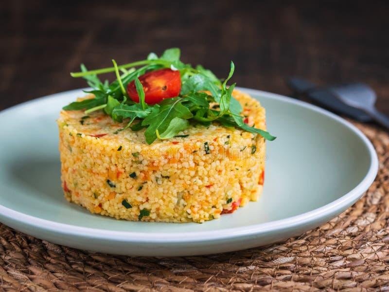 Salada deliciosa do taboulé do cuscuz do vegetariano com os vegetais, decorados com rúcula e tomate de cereja imagens de stock
