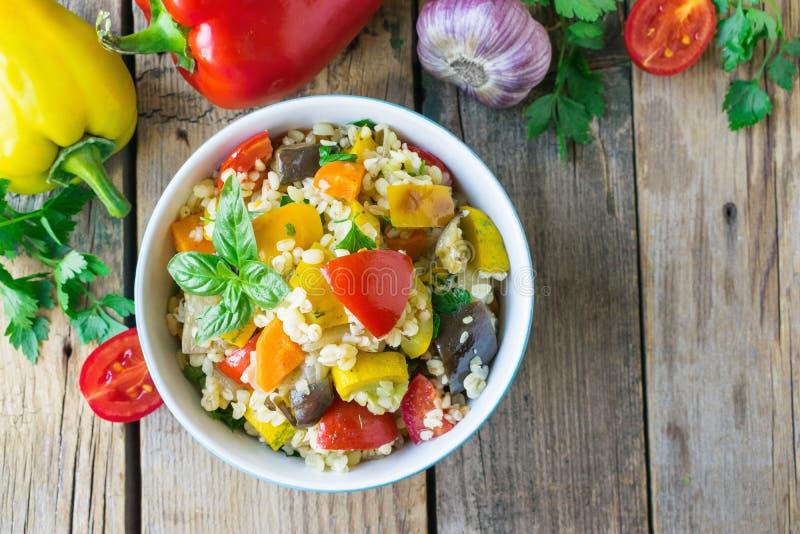 Salada do Bulgur com vegetais Bulgur com vegetais Fundo de madeira imagem de stock