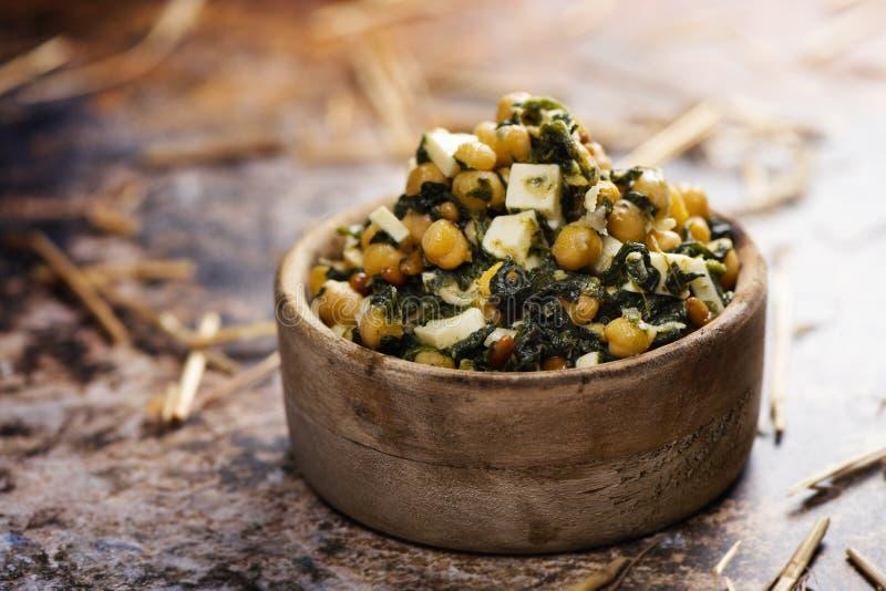 Salada do grão-de-bico, com espinafres, pinhões e queijo imagem de stock