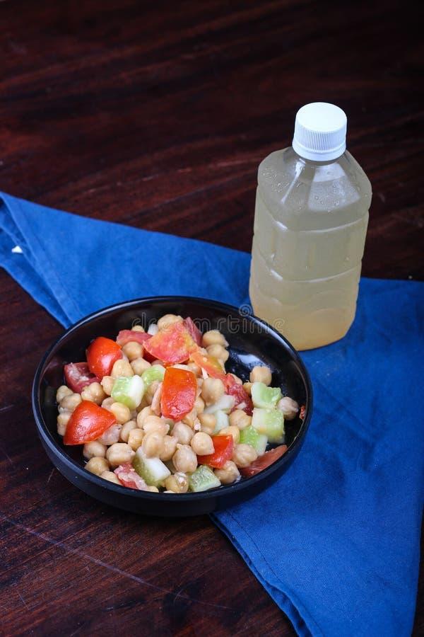 Salada do grão-de-bico lanç com tomate e pepino; acompanhado com bebida fresca do gengibre imagens de stock