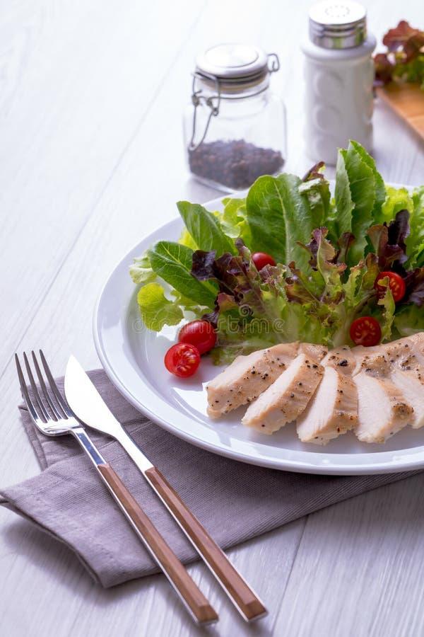Salada do peito de frango em uma placa branca com forquilha e faca fotografia de stock
