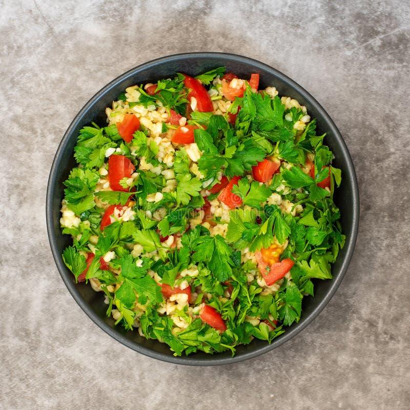 Salada do taboul? com bulgur, salsa, cebola da mola e tomate na bacia no fundo cinzento Vista superior imagens de stock