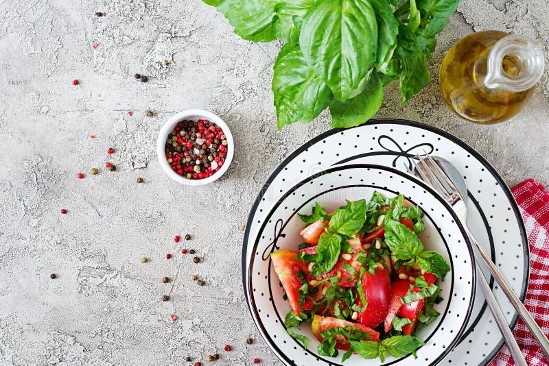 Salada do tomate com manjericão e pinhões na bacia - aperitivo saudável do alimento biológico da dieta do vegetariano do vegetari imagem de stock