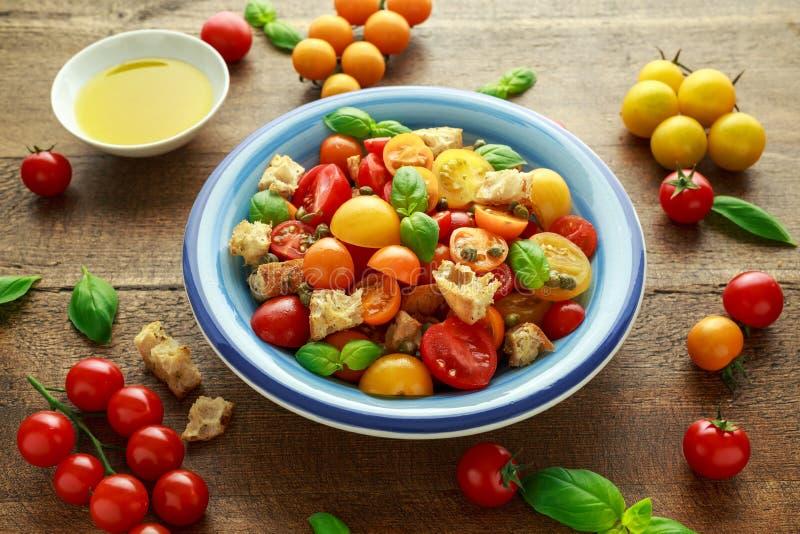 Salada do tomate de Panzanella com os tomates de cereja, as alcaparras, manjericão e o pão torrado vermelhos, amarelos, alaranjad foto de stock