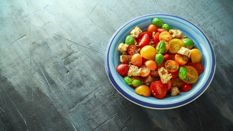 Salada do tomate de Panzanella com os tomates de cereja, as alcaparras, manjericão e o pão torrado vermelhos, amarelos, alaranjad fotos de stock