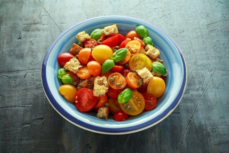 Salada do tomate de Panzanella com os tomates de cereja, as alcaparras, manjericão e o pão torrado vermelhos, amarelos, alaranjad fotos de stock royalty free