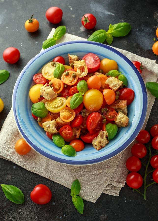 Salada do tomate de Panzanella com os tomates de cereja, as alcaparras, manjericão e o pão torrado vermelhos, amarelos, alaranjad imagens de stock royalty free