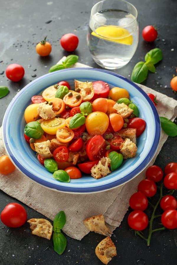 Salada do tomate de Panzanella com os tomates de cereja, as alcaparras, manjericão e o pão torrado vermelhos, amarelos, alaranjad imagem de stock royalty free