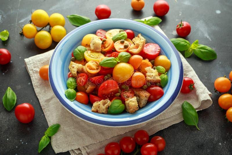 Salada do tomate de Panzanella com os tomates de cereja, as alcaparras, manjericão e o pão torrado vermelhos, amarelos, alaranjad foto de stock royalty free