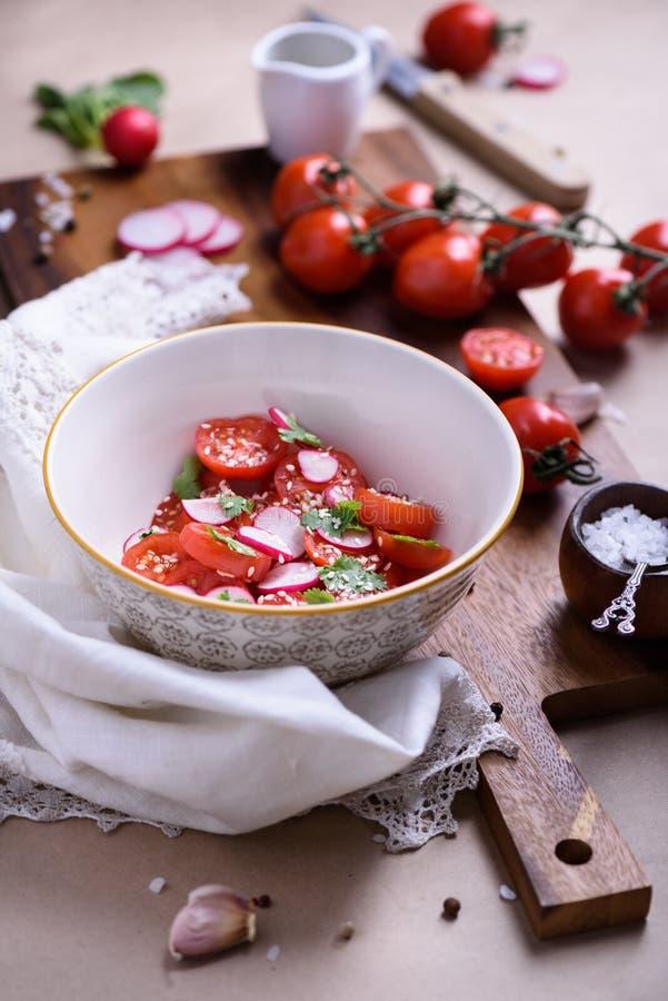 Salada do tomate do close-up com os ingredientes deliciosos coloridos no fundo Bio alimento, ervas e especiarias saudáveis Vegeta imagem de stock