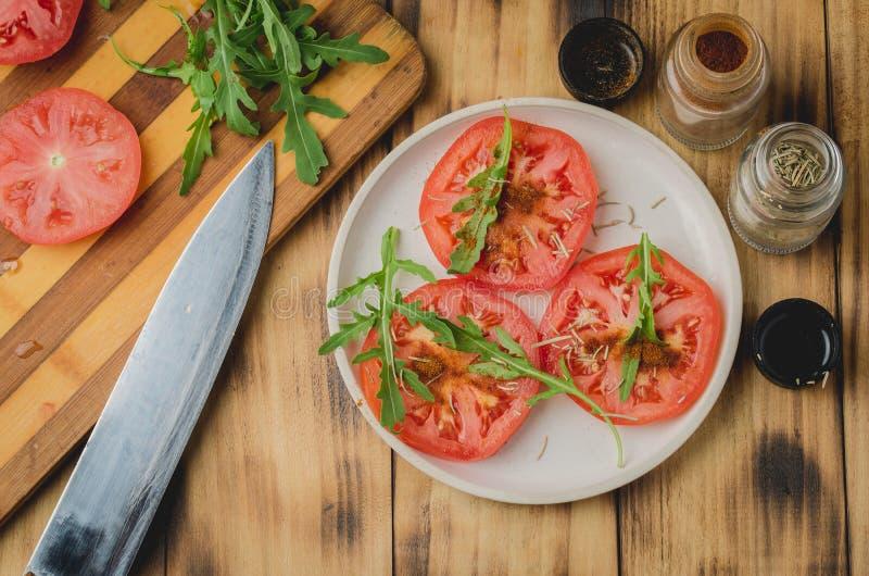 Salada do vegetariano Tomate com rúcula e temperos em uma bacia branca em um fundo de madeira Vista superior fotografia de stock