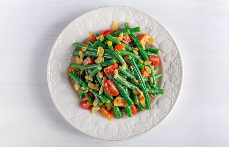 Salada dos feijões verdes com bruschettas, vermelho, os tomates amarelos e a amêndoa lascada na placa branca imagens de stock royalty free