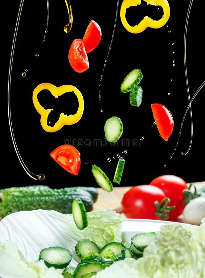 Salada dos ingredientes do voo isolada em um fundo preto Salada que flutua no ar acima da tabela Vegetais da alface fotos de stock royalty free