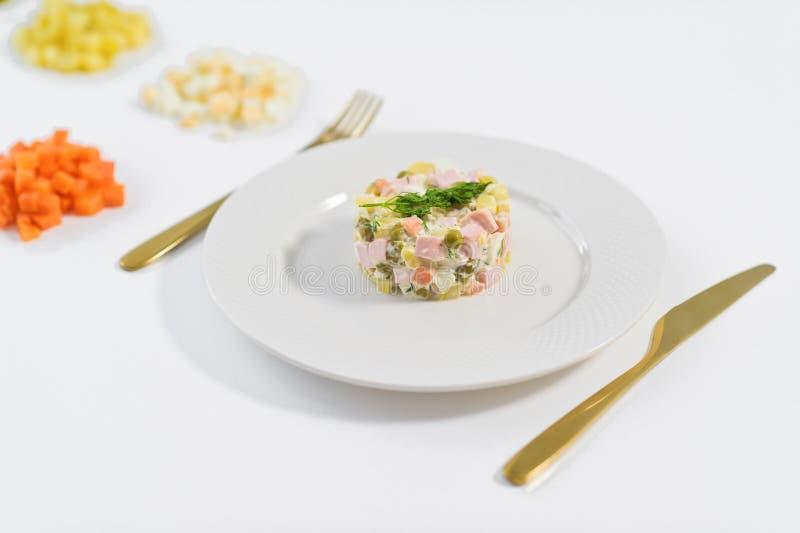 Salada e ingredientes de Olivier para cozinhar em um fundo branco foto de stock royalty free