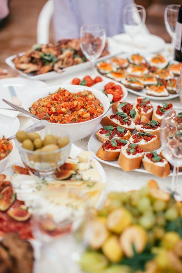 Salada e petisco e sandwitches diferentes na tabela branca Azeitonas de pé da refeição, queijo, frutos fotos de stock royalty free