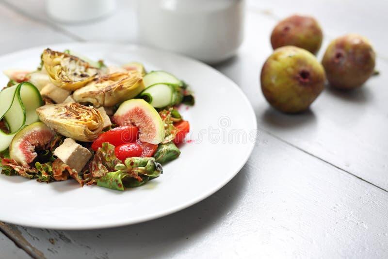 A salada excelente com figos, alcachofra, pepino, tomates, feta nas folhas da erva-benta cobriu com molho da framboesa imagens de stock