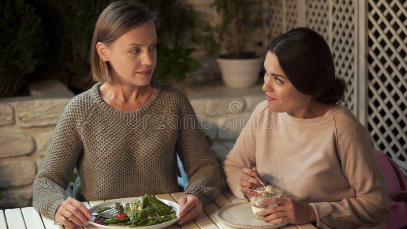 A salada fêmea do vegetariano comer, amigo prefere a sobremesa cremosa, escolhendo a nutrição imagens de stock