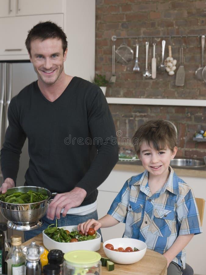 Salada feliz de And Son Preparing do pai no contador de cozinha fotos de stock