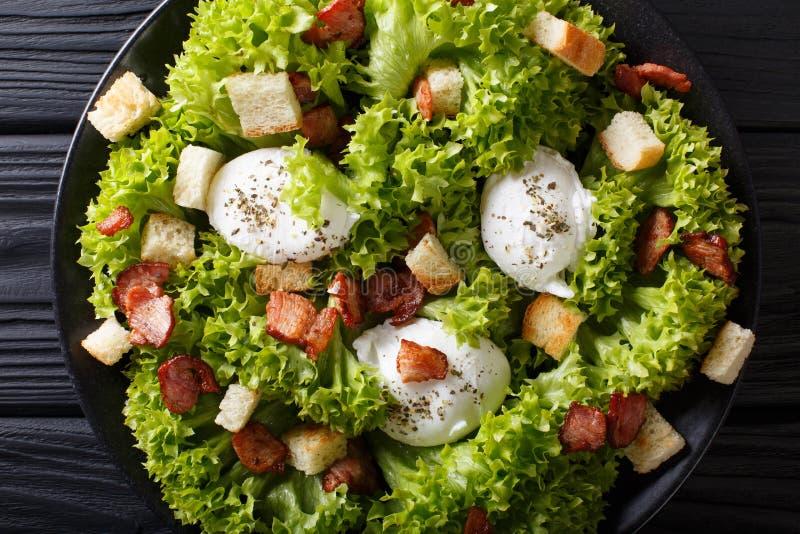 Salada francesa Lyonnaise com alface, bacon friável, pão torrado e foto de stock