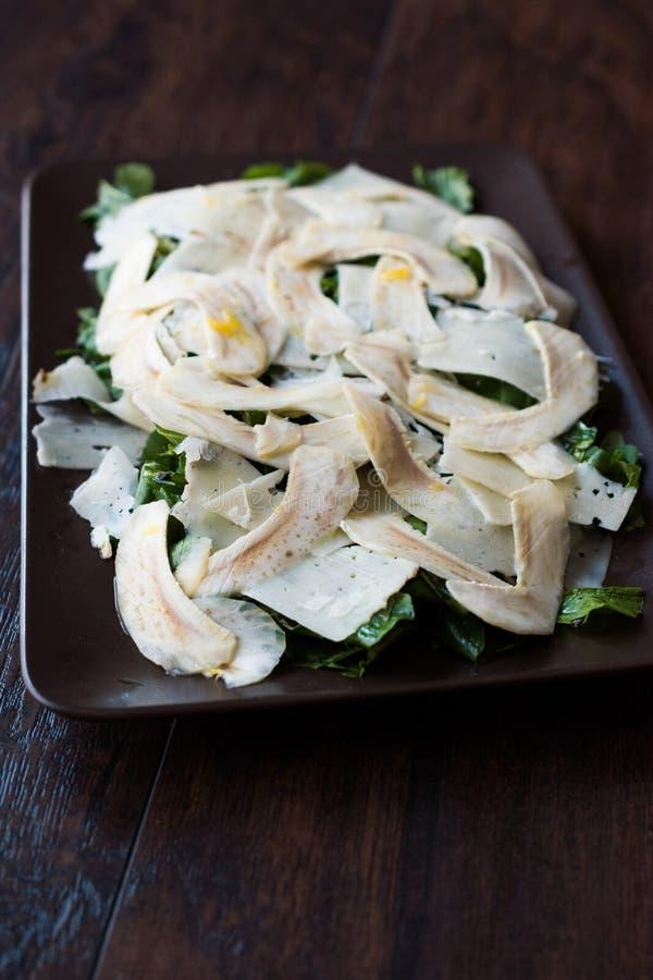 Salada fresca caseiro da alcachofra com r?cula, Rucola ou Rocket Leaves na superf?cie de madeira escura imagem de stock