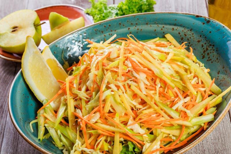 Salada fresca com maçã, cenoura, couve, aipo e limão no fim de madeira do fundo acima Alimento saudável imagem de stock