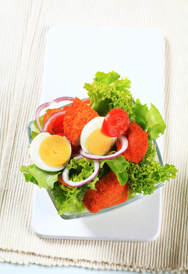 Salada fresca com queijo e o ovo panados fritados fotografia de stock royalty free