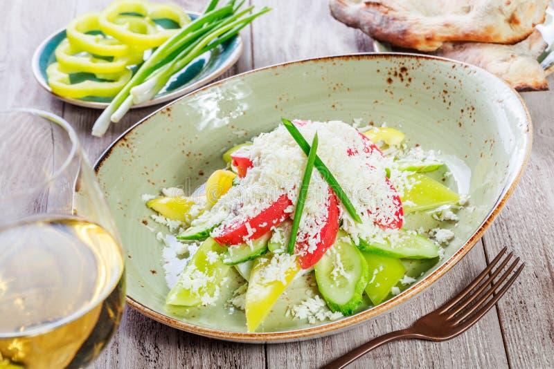 Salada fresca com tomates de cereja, pepino, pimenta doce e queijo parmesão e vidro do vinho no fundo de madeira imagem de stock royalty free