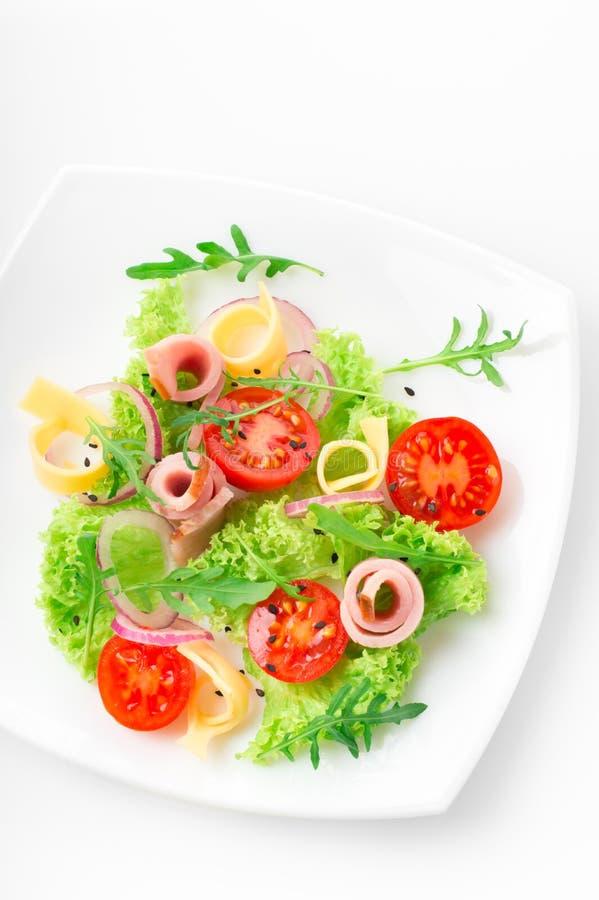 Salada fresca com tomates, rúcula, queijo e presunto na placa branca e no fundo branco fotos de stock royalty free