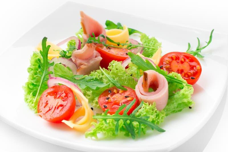 Salada fresca com tomates, rúcula, queijo e presunto na placa branca e no fundo branco fotografia de stock royalty free