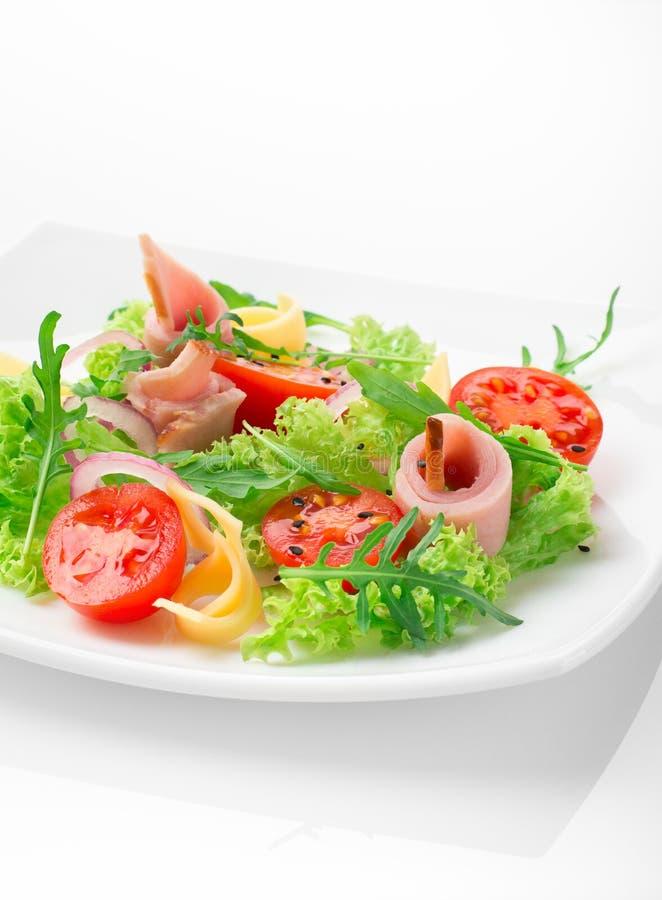 Salada fresca com tomates, rúcula, queijo e presunto na placa branca e no fundo branco imagens de stock