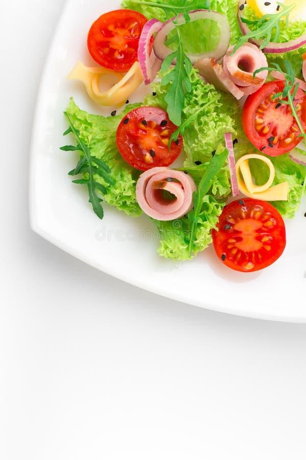 Salada fresca com tomates, rúcula, queijo e presunto na placa branca e no fundo branco imagem de stock royalty free