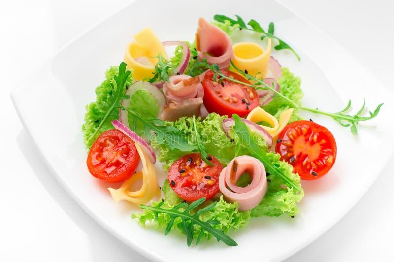 Salada fresca com tomates, rúcula, queijo e presunto na placa branca e no fundo branco imagens de stock royalty free