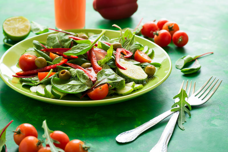 Salada fresca da mola com rúcula, espinafres, folhas da beterraba, tomates, fatias do pepino e pimenta doce foto de stock